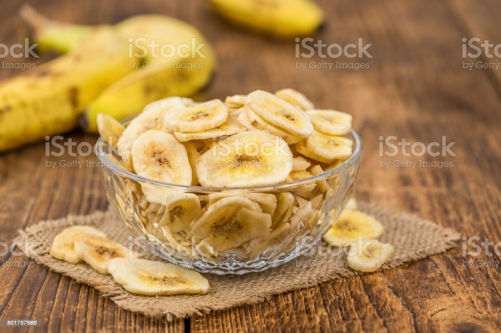 Dried Banana Chips on wooden background; selective focus stock photo