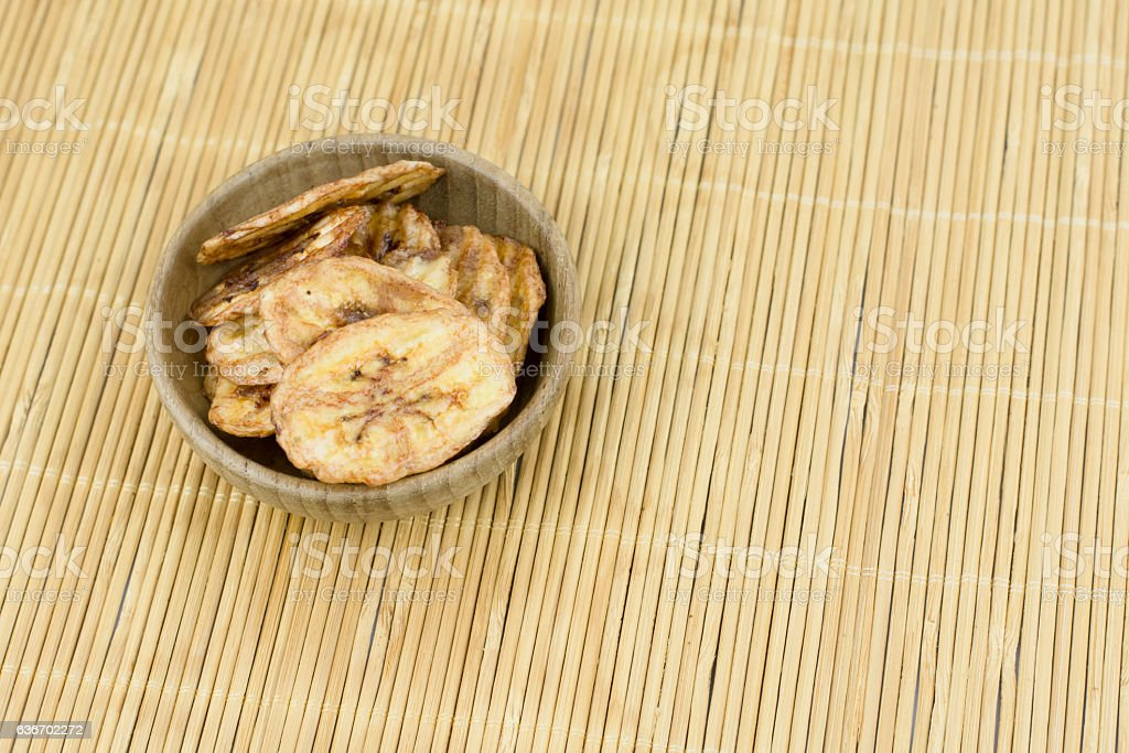 Dried banana slices in bowl wood  isolated on white background stock photo