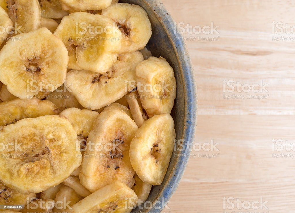 Dried bananas in an old bowl on a table stock photo