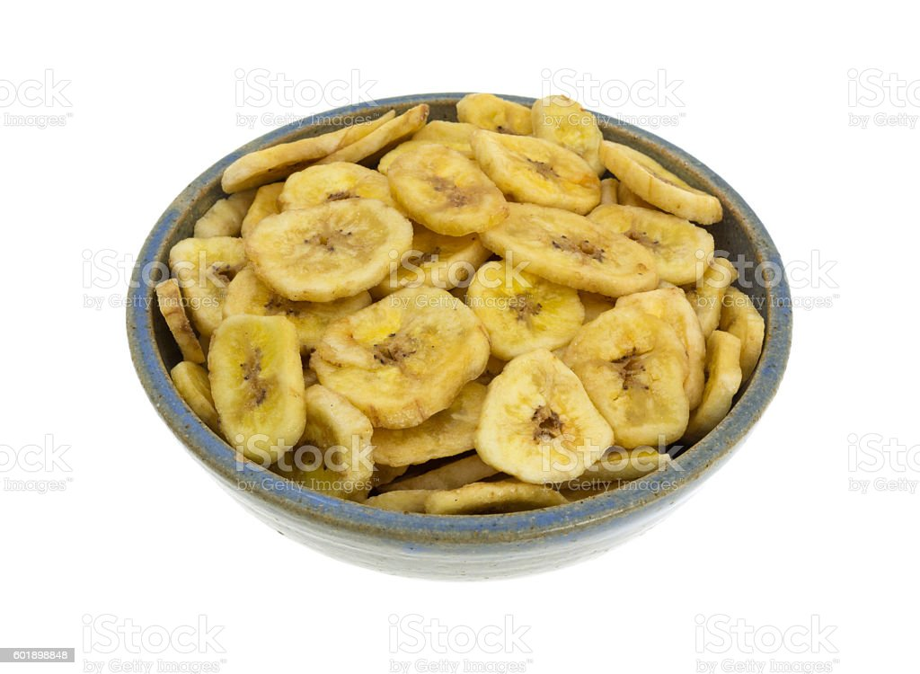 Dried bananas in an old bowl on white background stock photo