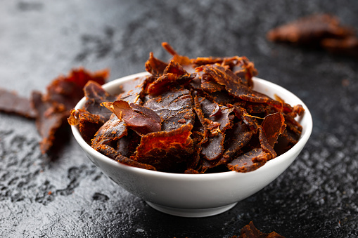 Dried Beef Jerky snack in white bowl.