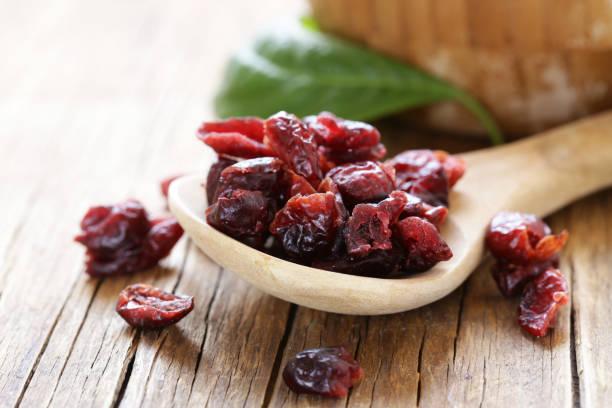 dried berries red cranberries on a wooden table - suszony produkt zdjęcia i obrazy z banku zdjęć