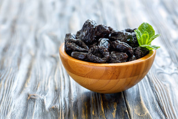 Dried black plums in a wooden bowl. stock photo