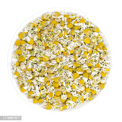 Dried chamomile blossoms in white bowl. Camomile tea, flowers of Matricaria chamomilla, used for herbal infusions and in traditional medicine. Closeup, from above, over white, isolated macro photo.