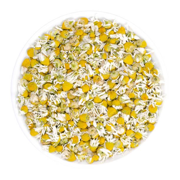 Dried chamomile blossoms, camomile tea in white bowl stock photo