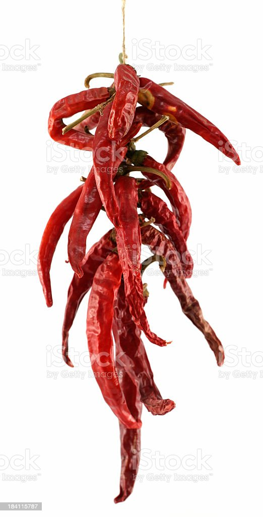 Dried chili peppers hanging from string on white background stock photo