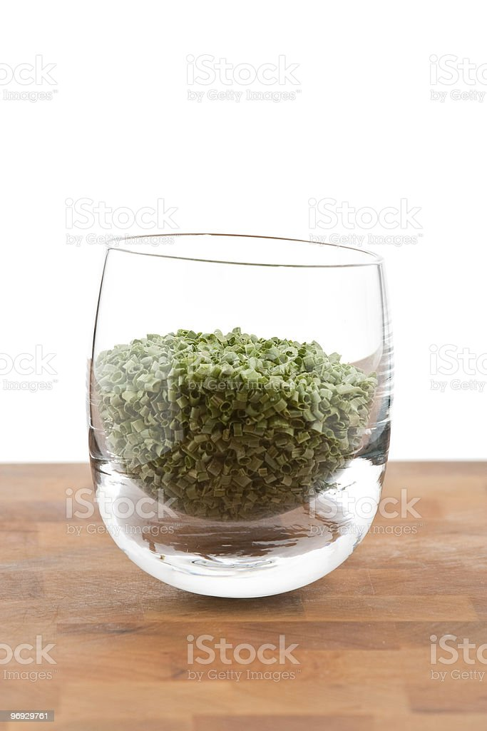 dried chive in glass on wooden table royalty-free stock photo