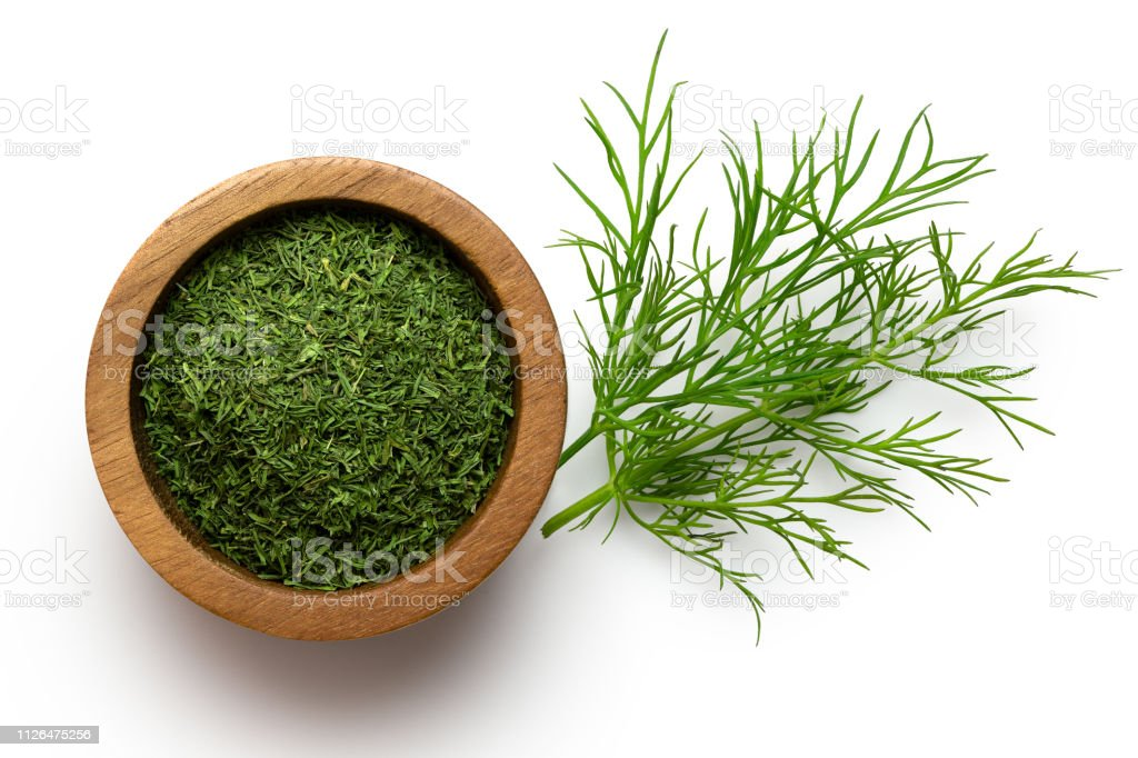 Dried chopped dill in a dark wood bowl next to fresh dill leaves isolated on white from above. - Zbiór zdjęć royalty-free (Biały)