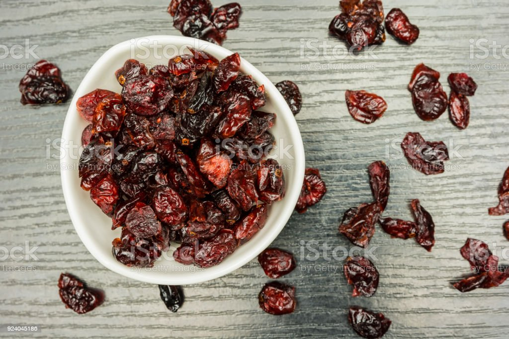 Dried cranberries in a bowl and scattered on a dark table. View from above. stock photo