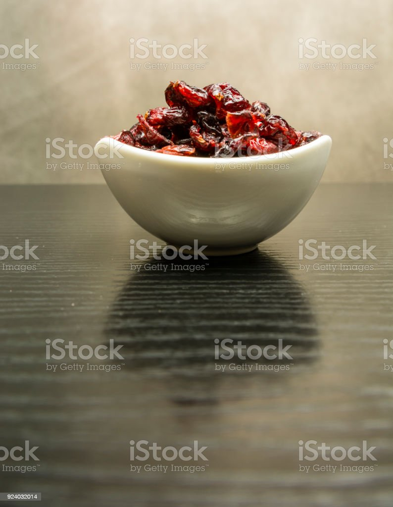 Dried cranberries in a white porcelain bowl. stock photo