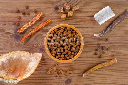 istock dried dog food in a bowl and different snack, chicken filet, antlers, lung, ear on white, flat lay 1153468010