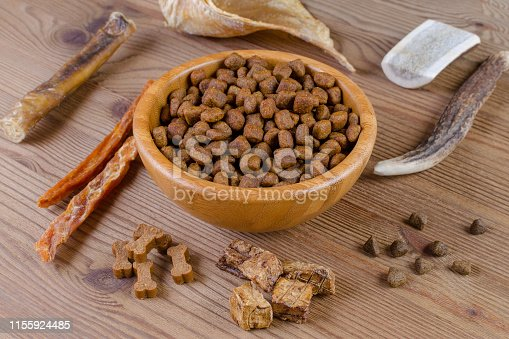 istock dried dog food in a bowl and different snack, chicken filet, antlers, lung, ear on wooden background 1155924485