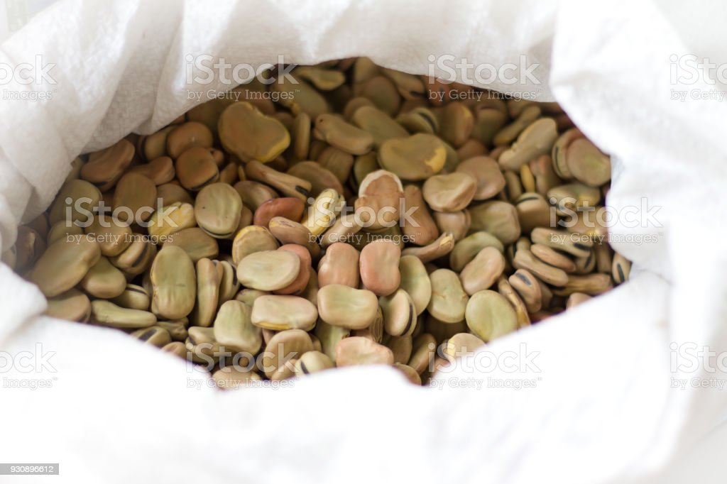 Dried Fava Beans in White Sack (Close-Up) stock photo