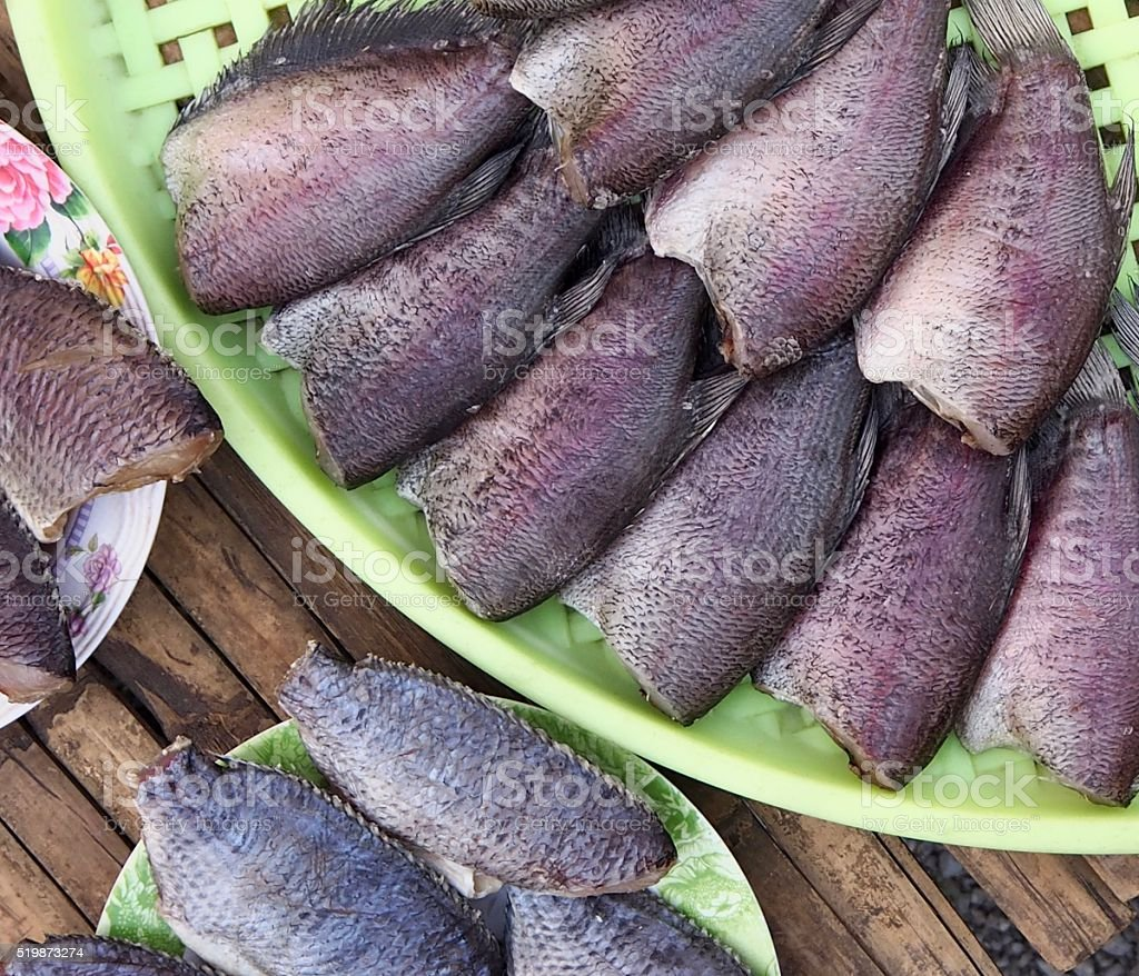 Dried fish from street vendor on green tray stock photo