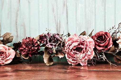 Dried floral arrangement, decor on wooden table.