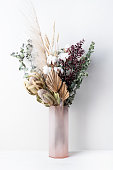 stylish modern dried flower arrangement in a pink vase. Eucalyptus leaves, banksia, cotton flower ,gold palm, pampas grass and ruscus leaves. Art deco Boho gift for Anniversary, birthday, Mother's Day, Valentine's Day or any celebration.