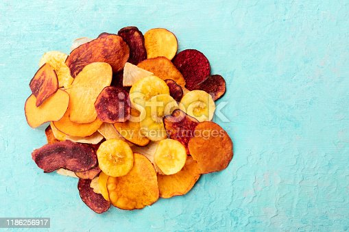 Dried fruit and vegetable chips, healthy vegan snack, a mixed heap on a teal background, top shot with a place for text