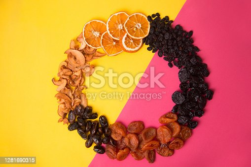 Dried fruit circle frame on bright yellow pink background