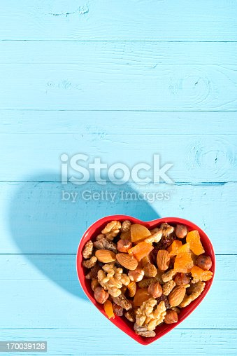 Dried fruits and nuts in a heart shaped bowl.