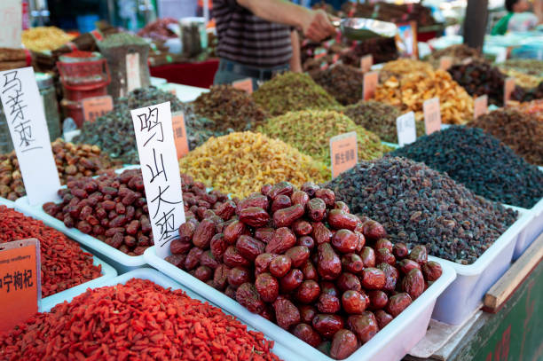 Dried fruits being sold in a market stall at a street market in the city of Dunhuang stock photo