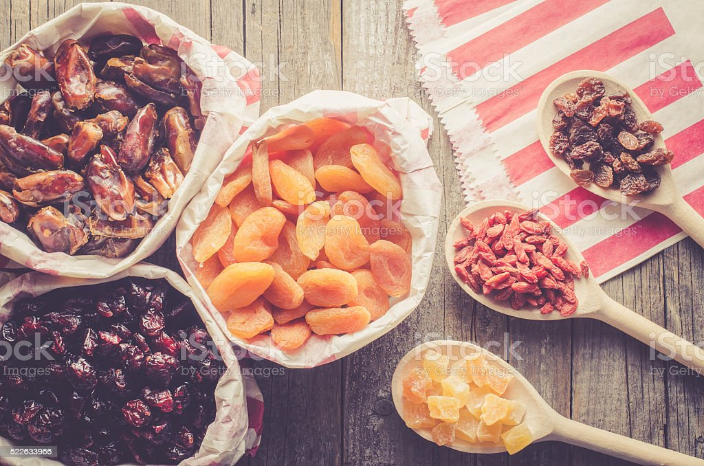 Dried fruits in paper bag on wooden table stock photo