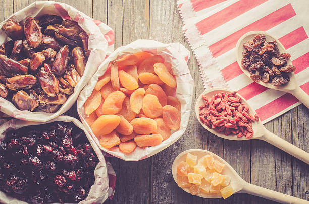 dried fruits in paper bag on wooden table - dried fruit stock photos and pictures