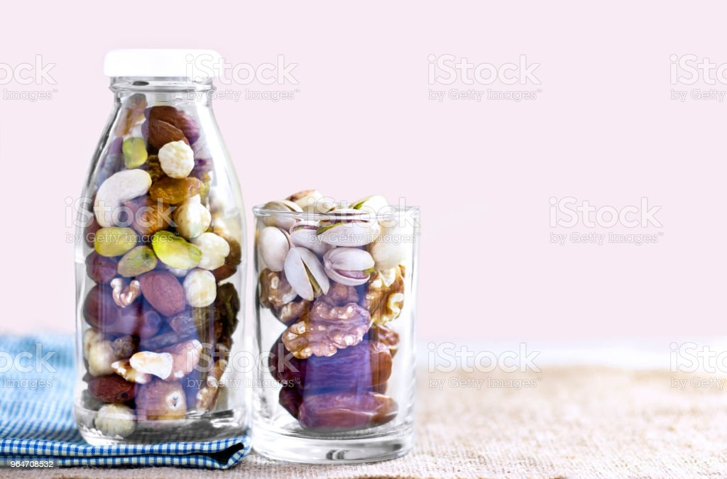 Dried fruits mix and variety of nuts in a bottle and glass on the brown sackcloth. with copy space for your text. royalty-free stock photo