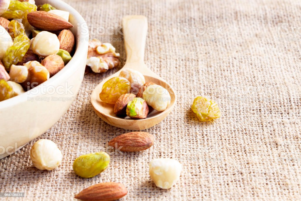 Dried fruits mix and variety of nuts in wooden spoon on sackcloth.  with copy space for your text. royalty-free stock photo