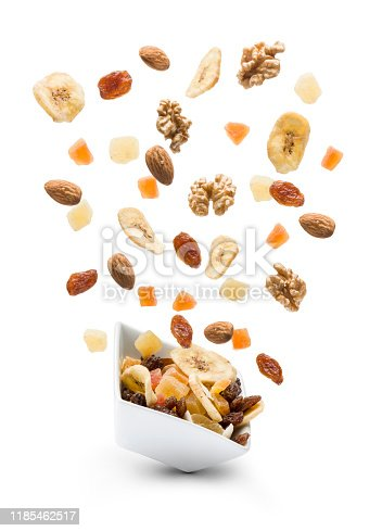 Dried fruits jumping out white bowl on white background