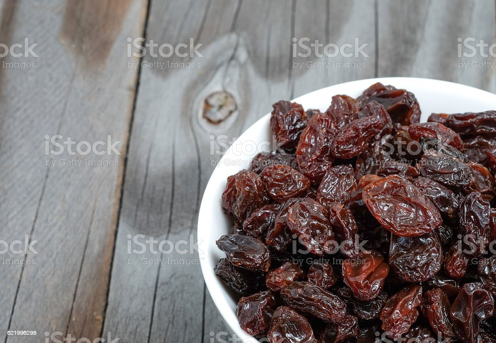 Dried grapes in white cup on wooden floor. stock photo