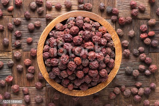 dried hawthorn berries in bowl on wooden table background.