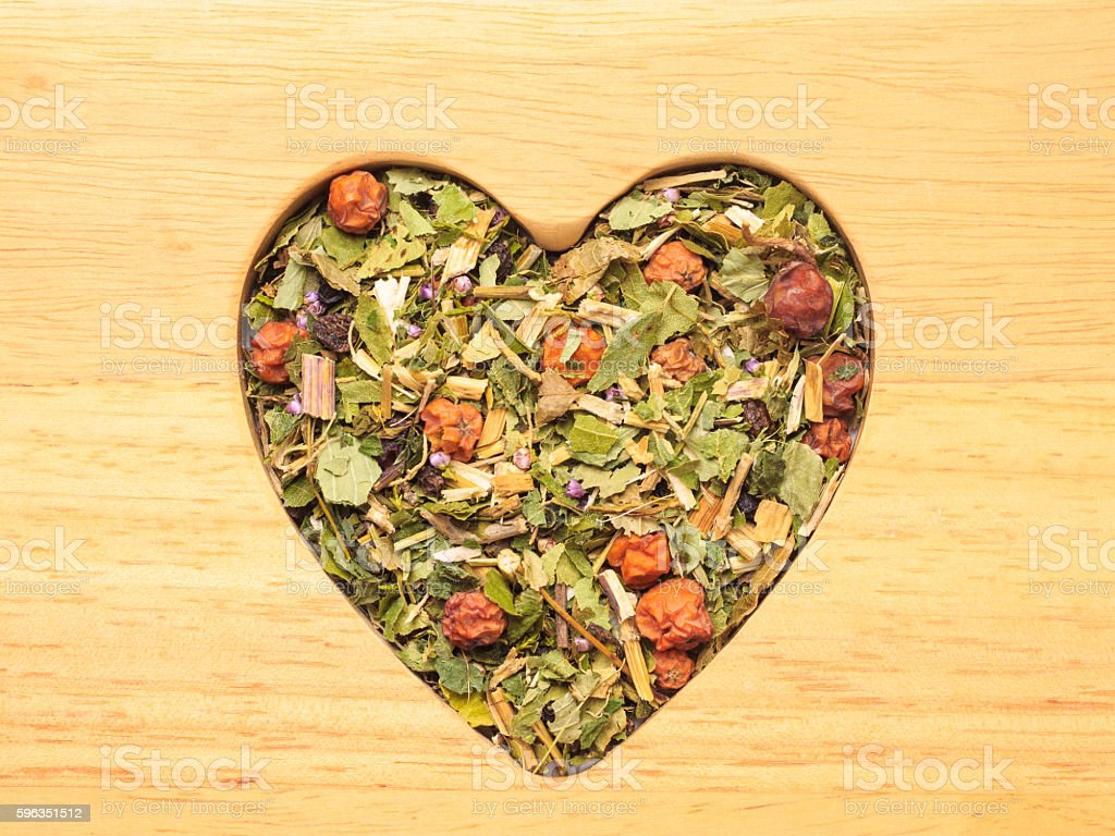 Dried herb leaves heart shaped on wooden surface royalty-free stock photo