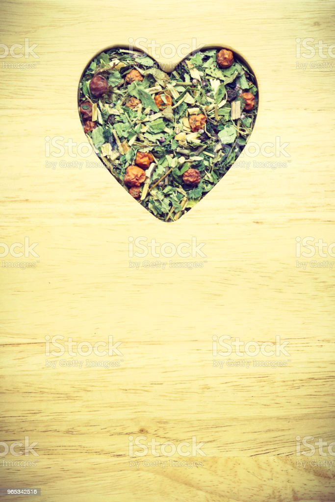 Dried herb leaves heart shaped on wooden surface zbiór zdjęć royalty-free
