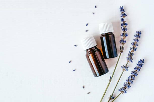 dried lavender with a bottle of essential oil - colore lavanda foto e immagini stock