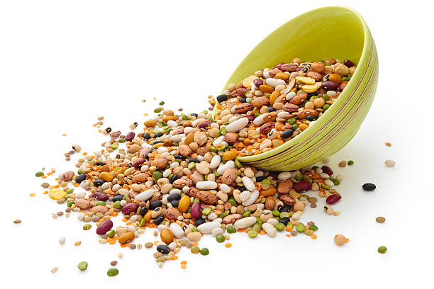 Dried legumes and cereals in green bowl stock photo