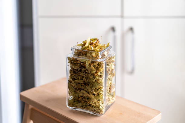 dried linden flowers in a jar macro view stock photo