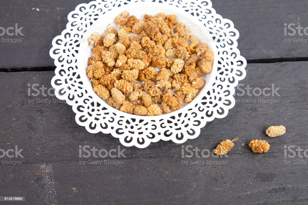 Dried mulberries on wooden background stock photo