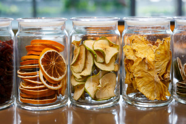 Dried oranges and apples in glass jars. stock photo