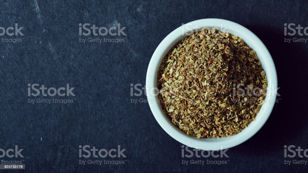 Dried oregano herbs in white bowl stock photo