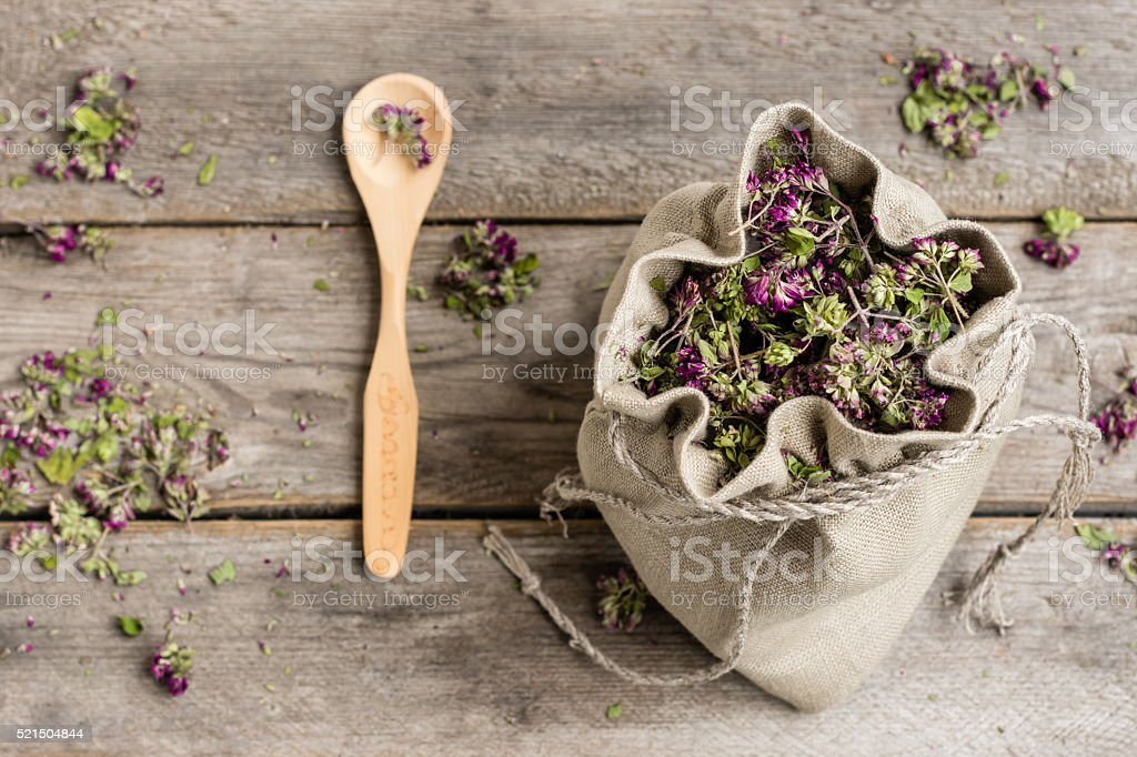 Dried oregano in a linen bag on a wooden gray table stock photo