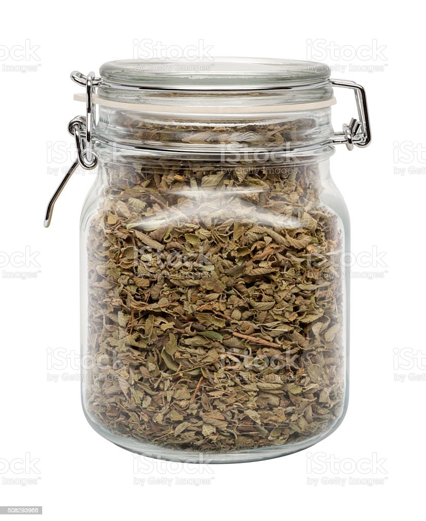 Dried Oregano Leaves in a Glass Canister with a Metal Clamp. The...