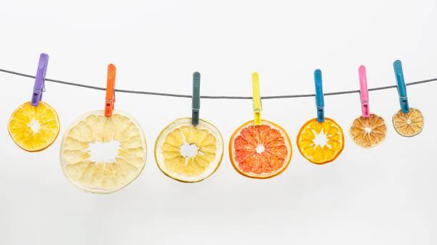 getrocknete stücke von zitrusfrüchten hängen wäscheklammern auf weißem hintergrund - orangenscheiben trocknen stock-fotos und bilder