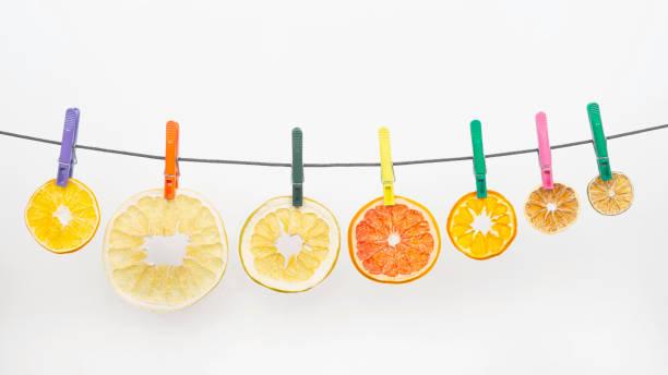 getrocknete stücke von zitrusfrüchten hängen auf wäscheklammern auf weißem hintergrund - orangenscheiben trocknen stock-fotos und bilder