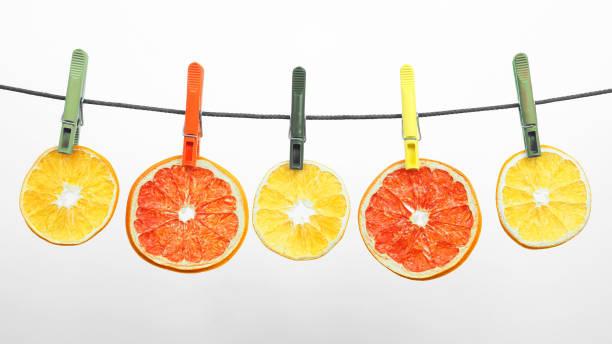 getrocknete stücke von zitrusfrüchten hängen an wäscheklammern - orangenscheiben trocknen stock-fotos und bilder