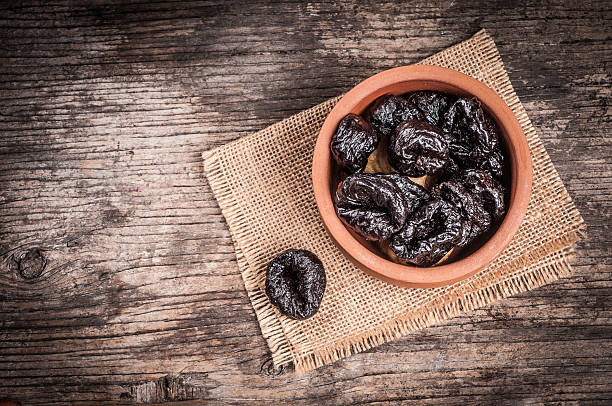 Dried plums in clay bowl stock photo