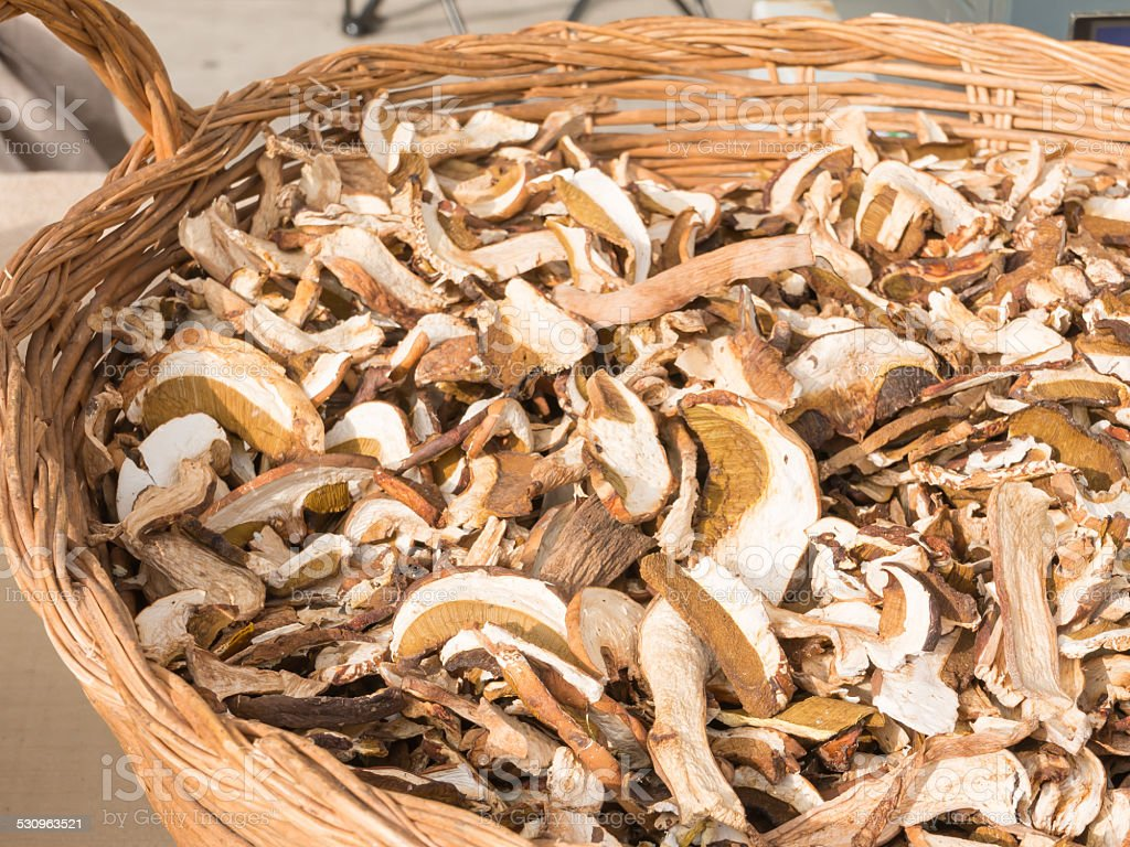 dried porcini mushrooms in wicker bowl stock photo