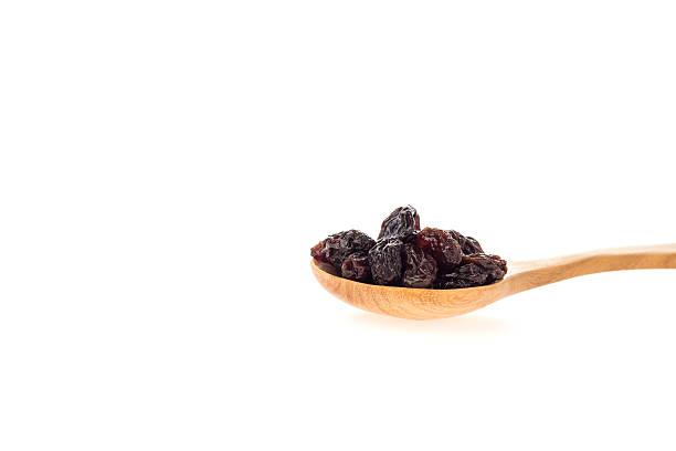 dried raisins in wooden spoon. - grape sugar stock-fotos und bilder