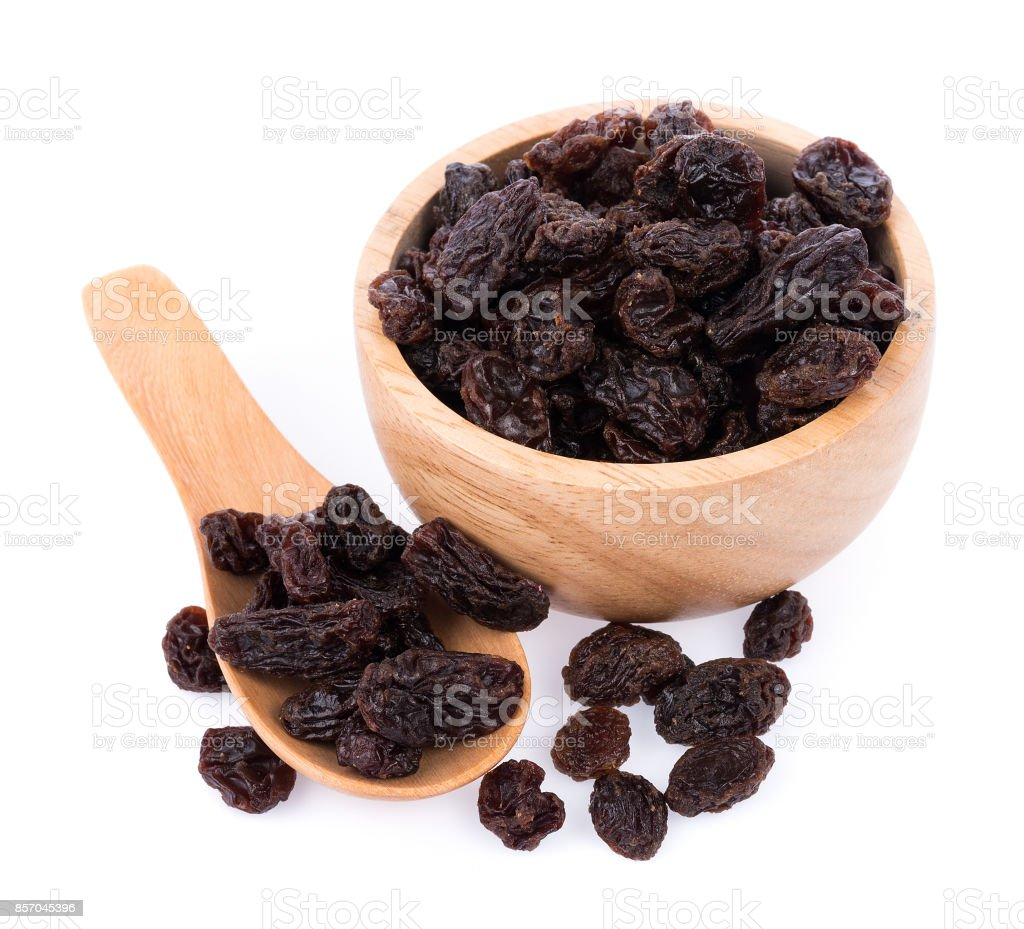 Dried raisins on Wooden Spoon on white stock photo