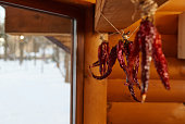 Dried red chili pepper hanging from a rope on a wooden wall