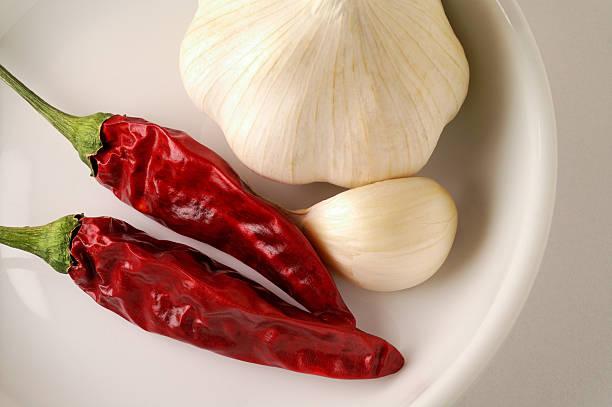 getrocknete red hot peppers und knoblauch auf gericht - peperoni stiche stock-fotos und bilder